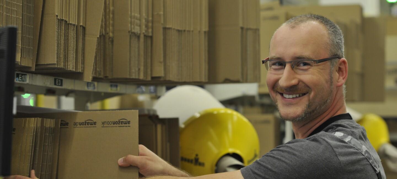 Ein Mitarbeiter im Logistikzentrum an einer Packstation