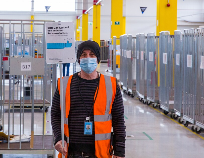 Mitarbeiter mit Sicherheitsweste und Schutzmaske