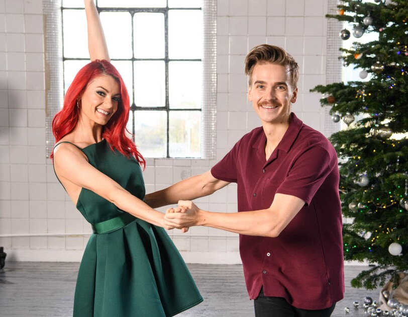 Dianne Buswell and  Joe Sugg dancing in a studio, behind them is a Christmas tree.