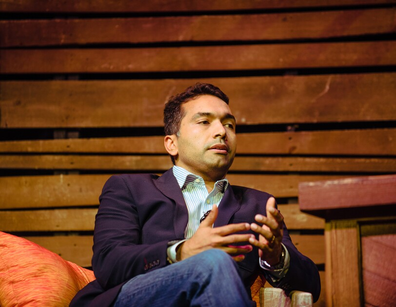 """A man, Maju Kuruvilla, is seated on stage during Amazon """"Live at the Ryman"""" event."""