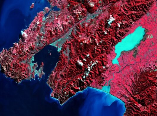 A satellite image showing a red land mass surrounded by a blue body of water illustrates insights provided by ASDI.