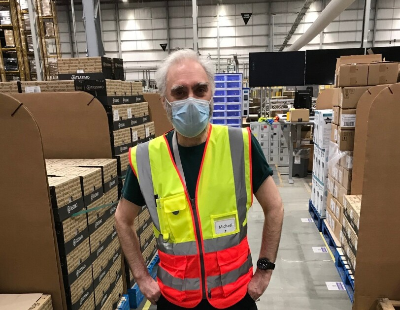 Michael Power, temp flow director, standing in the fulfilment centre while wearing a facemask and a hi-vis jacket.