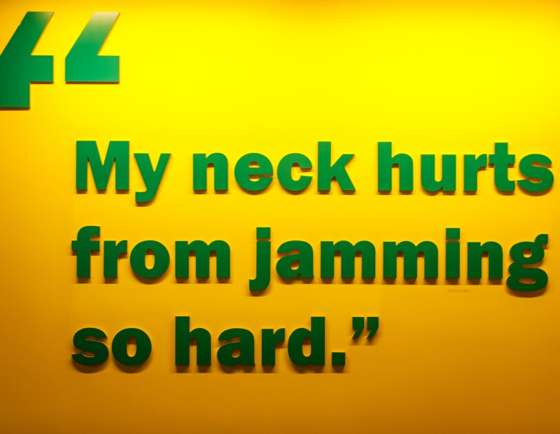 "A quote in green lettering on an orange wall at the Amazon Music office in Seattle, WA. It reads ""my neck hurts from jamming so hard."""