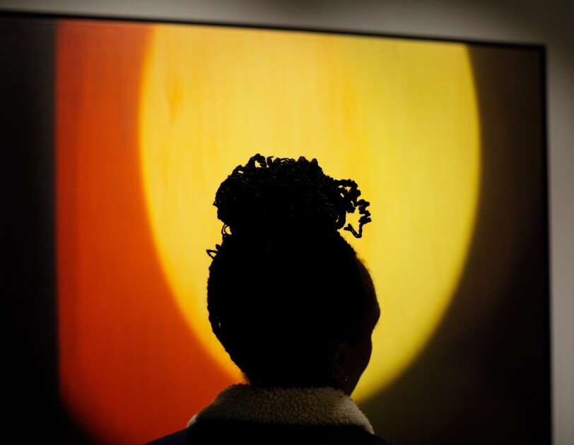 A silhouetted woman stares at a piece of art. The art is a yellow circle with an orange border on a black canvas.