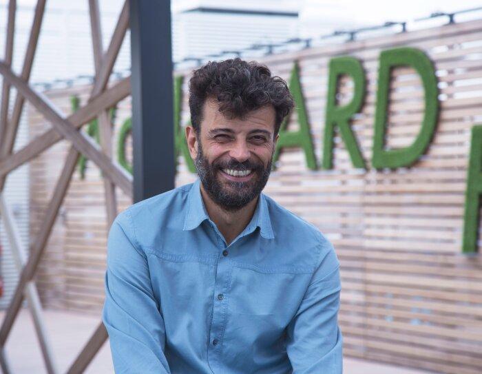 Alessandro Saccon, PR Manager di Amazon, sorride in primo sul terrazzo degli uffici Amazon di Milano. Sullo sfondo uno scorcio del terrazzo, con alcune lettere del motto 'Work hard' di Amazon.