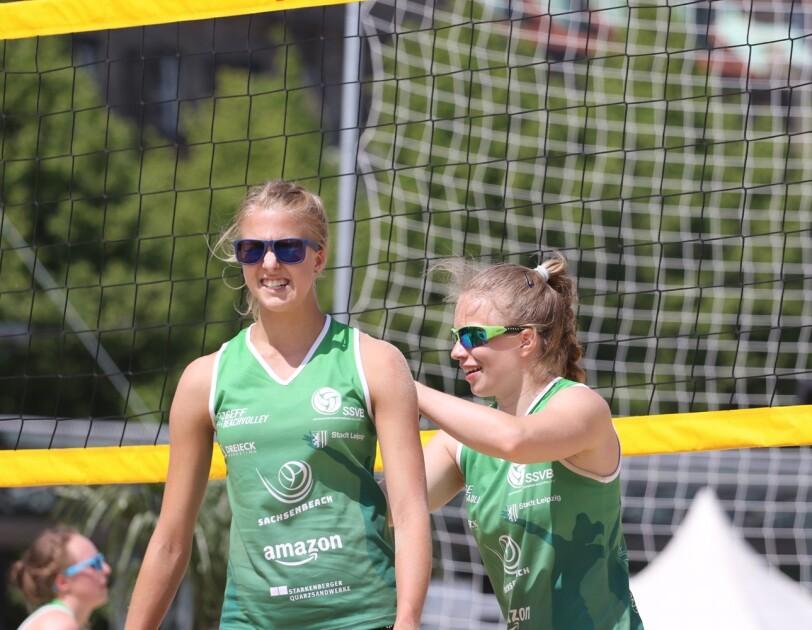 """Zwei Beachvolleyballerinnen stehen am Netz, beide in grünen Trikots u. a. mit Aufdruck """"Amazon"""". Sie tragen Sonnenbrillen."""