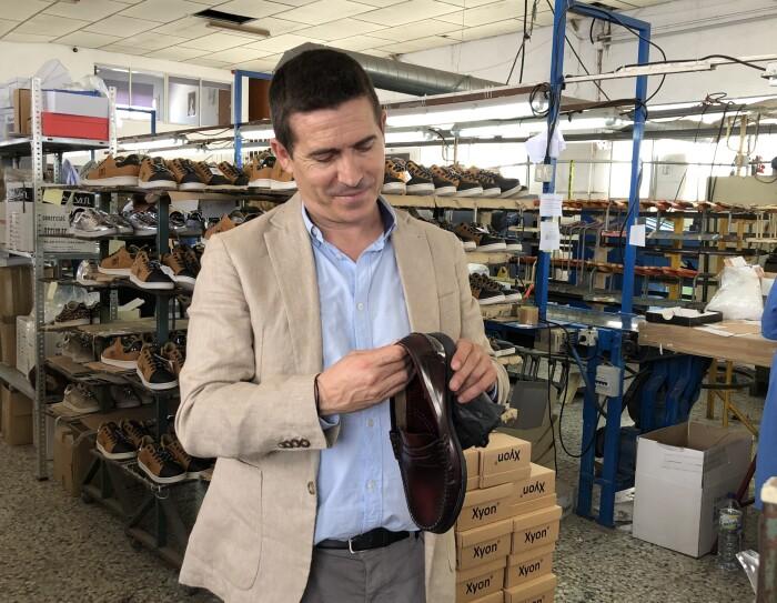 José Antonio Mollá, fundador de Castellanisimos, en una de sus fábricas, observando un zapato castellano que tiene en sus mannos. Detrás hay cahas de zapatos y una persona trabajando en una mesa.