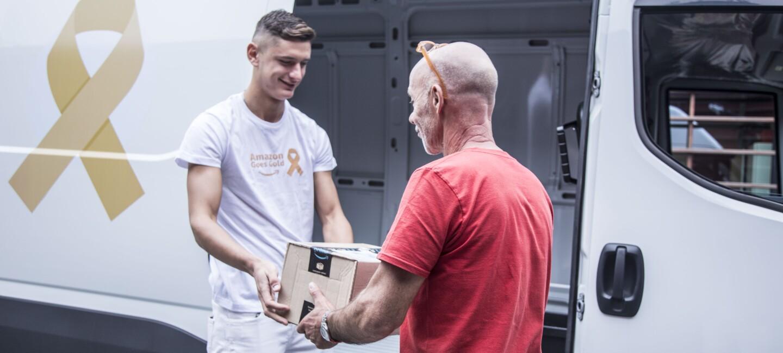 Il corriere Emanuele Gazzera consegna un pacco a un volontario di CasaOz. Sullo sfondo il furgone brandizzato con il logo d'oro delle attività Amazon Goes Gold.