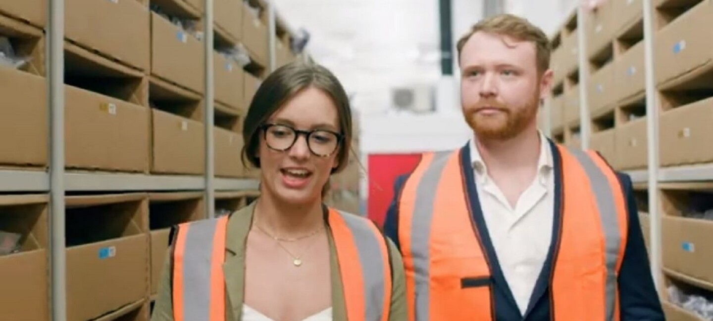 Woman and a man in high-vis walking through a warehouse eisle