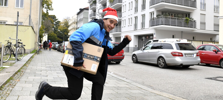 Ein junger Mann in Amazon-Zusteller-Kleidung mit roter Weihnachtszipfelmütze: Er hält ein Amazon Paket in der Hand.