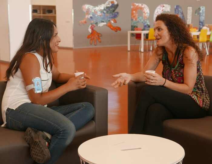 Karla Elena Márquez y su amiga y compañera de trabajo, Eva Collados, conversan en uns sofás negros de la cantina de un centro logístico de Amazon. Cada una está sentada en un sofá negro y sujeta un vaso de café. Tienen un mesa blanca en el centro y de fondo se ven sillas y mesas y la salamandra de Gaudí en la pared. Karla Elena lleva unos jeans y una camisa blanca sin mangas y el pelo suelto. Eva lleva un pantalón negro, una camisa estampada sin mangas y también lleva el pelo suelo.