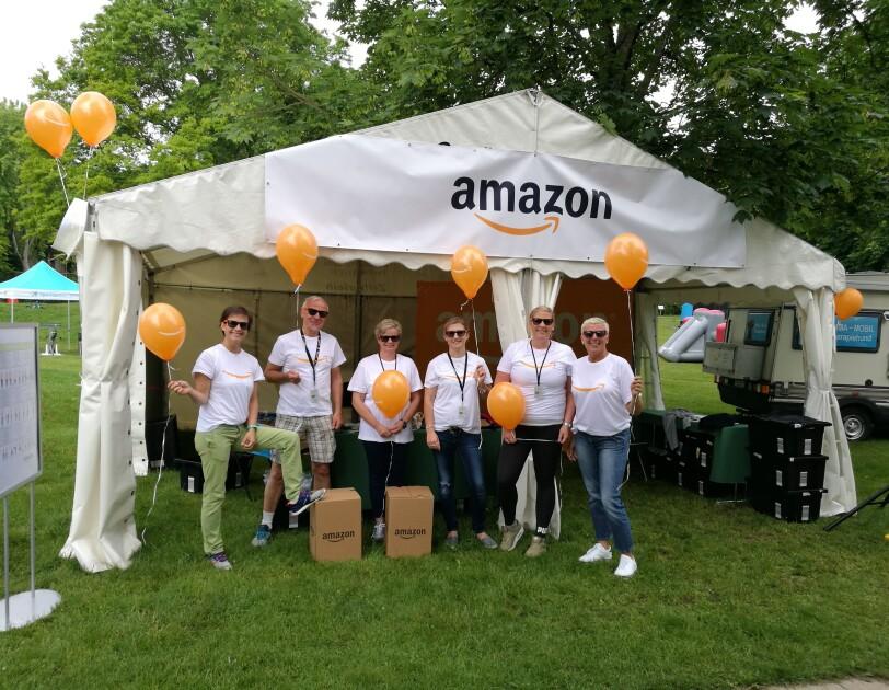 Eine Gruppe von Mitarbeitern in Amazon T-Shirts steht vor einem Zelt mit dem Amazon Logo. Einige tragen orange-farbene Luftballons.
