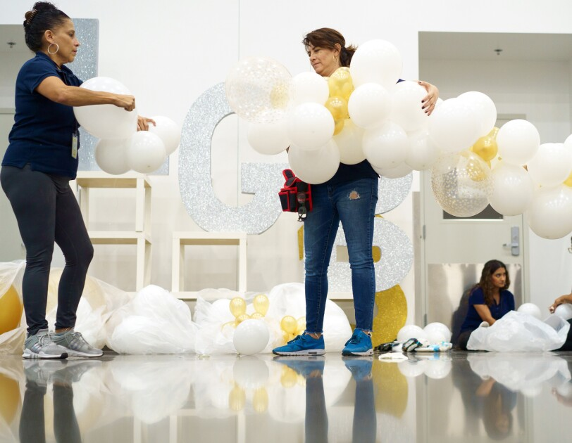 Women work to assemble decorations made out of white, gold, and sparkly balloons.