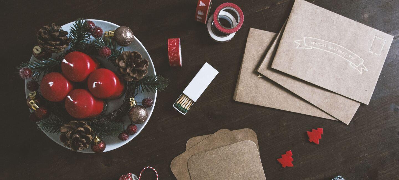 Auf einem Tisch liegen: Adventskranz, Braune Briefumschläge, Faden, Schere, Klebeband, Weihnachtsdeko und vieles mehr.