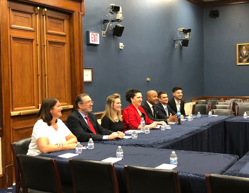 Small business owners, seated at a table, as they meet with political leaders in Washington D.C.