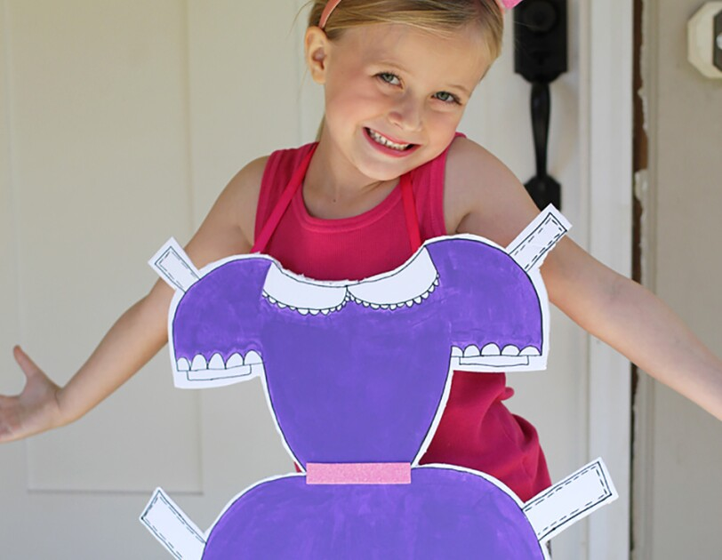 "A little girl in a ""paper doll"" costume. She wears a tank top and leggings, and wears a dress with tabs (like a paper doll dress) on her front."