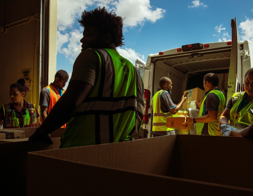 People in safety vests unload a delivery van.