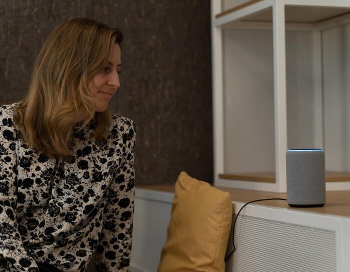 Marta Morales, Senior Product Manager de Alexa. Con una camisa estampada y el pelo castaño claro, Marta mira fijamente un dispositivo Echo de color gris colocado sobre un mueble en la parte derecha de la imagen.