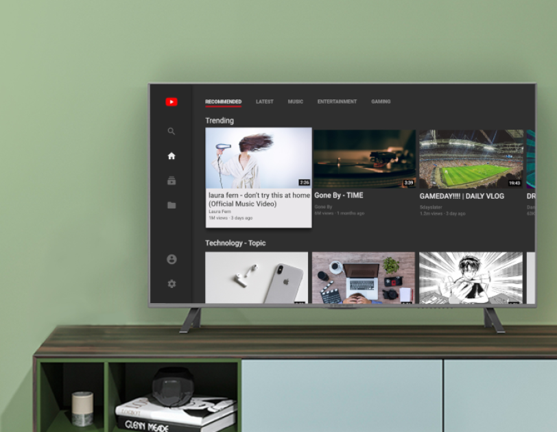 A television sits on a console table, with the television screen displaying the YouTube experience on Fire TV.