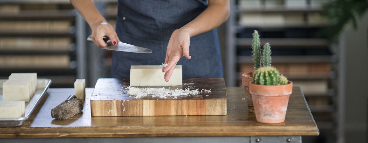 An employee at Little Flower Soap Company cuts a block of soap by hand, to create bars of soap to be packaged and shipped to customers.