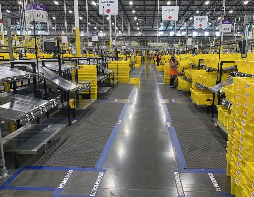 View inside an Amazon fulfillment center showing sort lines, with associates practicing social distancing.