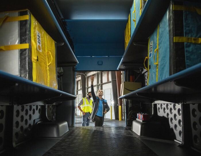 Due dipendenti Amazon ripresi dall'interno del furgone elettrico Rivian. Una donna sta aprendo il furgone e dietro di lei un uomo guarda l'interno del baule. Nel furgone vi sono dei pacchi Amazon.