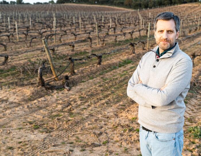 Fernando Rodríguez, CEO de Pradorey. En un viñedo en septiembre, cuando la viña está preparándose. Fernando está  en primer plano, cruzado de brazos, con unos jeans, un polo verde y una sudadera gris clara. Tiene los ojos verdes, pelo blnaco y subio corto y barba de dos días.