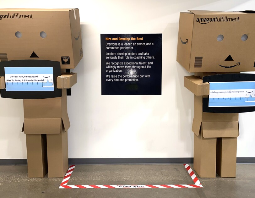 "Two ""box people"" made of cardboard stand in an Amazon fulfillment center. both of them are positioned 6 feet from one another, and hold signs that say ""Do your part, 6 feet apart"""