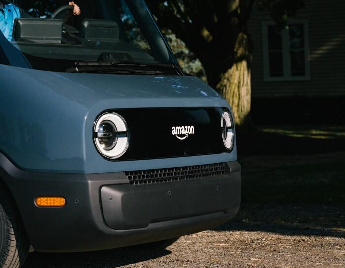 Primer plano de la parte frontal de la furgoneta Rivian. Aparecen los dos faros en blanco y en el centro del logo de Amazon también en blanco. La parte inferior de ventilación es de color negro.