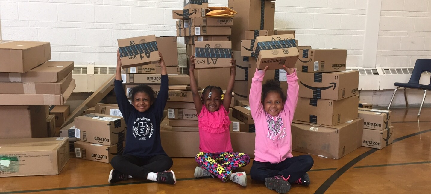 Three children holding Amazon delivery boxes over their hands and smiling. They are in a school gymnasium in Detroit, surrounded by Amazon boxes.