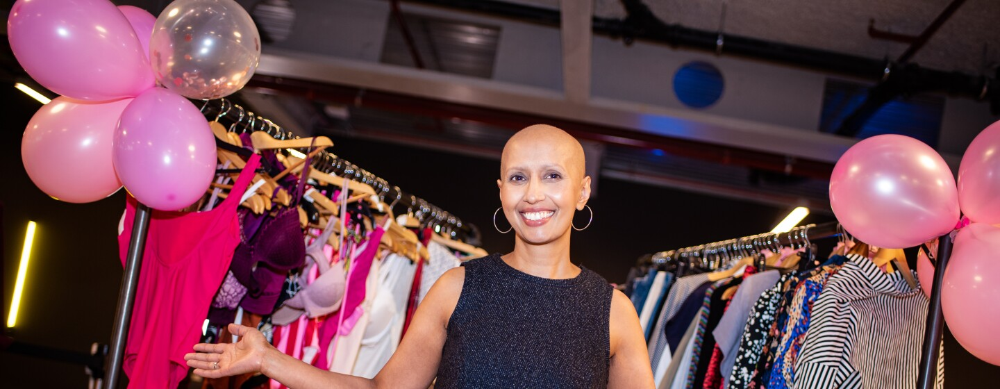Amazon Fashion Studio employee Balvinder Pawar smiling in front of several racks of clothes decorated with pink balloons at a charity sample sale.