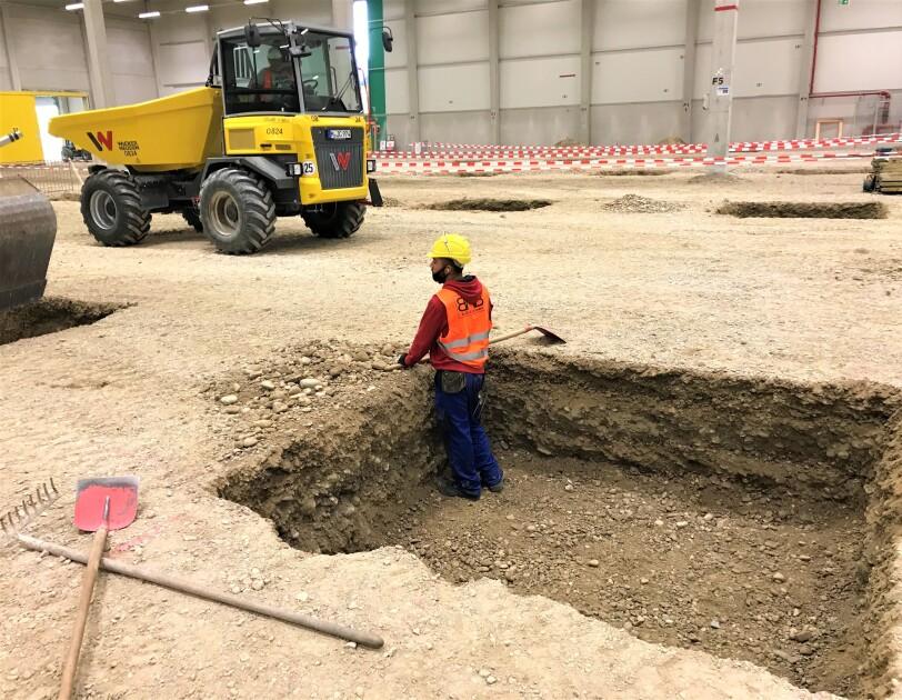 Ein Bauarbeiter steht hüfttief in einem Graben inmitten des Logistikzentrums