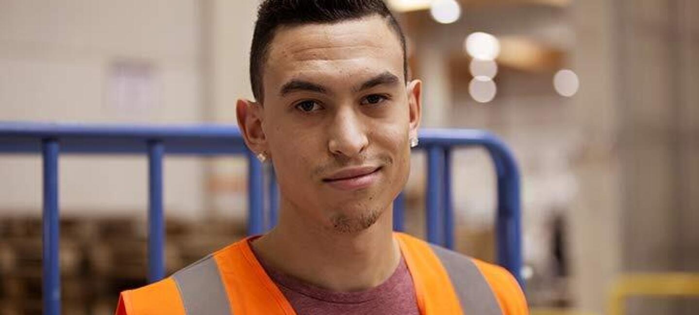 Un employé d'un centre de distribution d'Amzon en France sourit dans un décor de centre logistique. Il porte un gilet de sécurité.