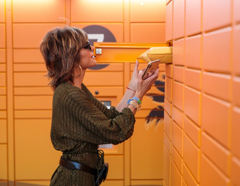 A woman looks inside a locker compartment and removes a package.