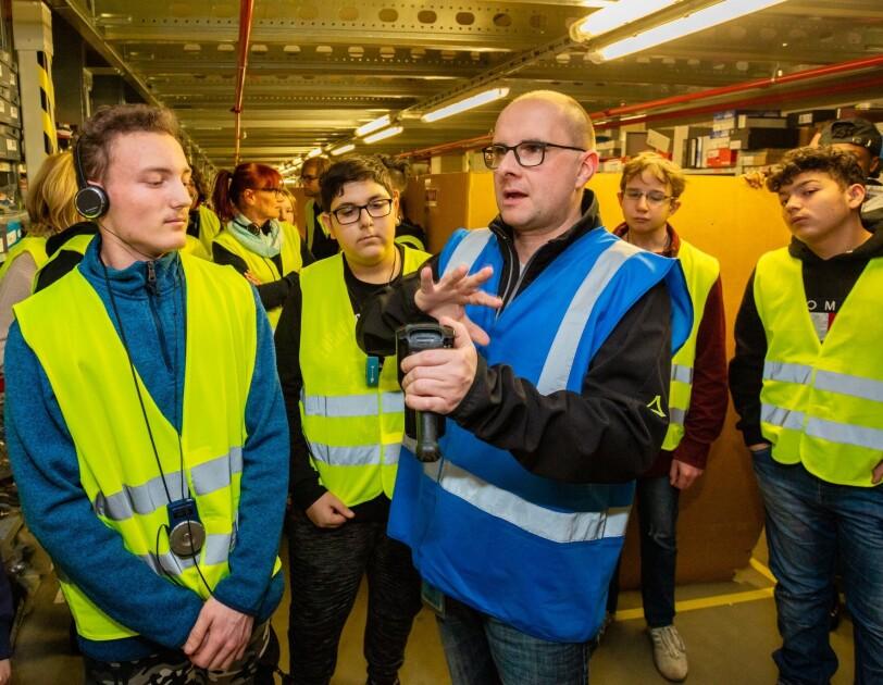 Ein Mann mit Brille und blauer Sicherheitsweste hält einen Scanner in der Hand. Ein Gruppe von SchülerInnen hat sich um ihn versammelt und hört ihm zu.