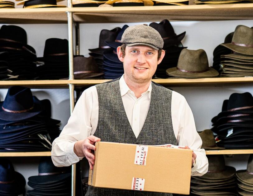 Ein Mann steht vor einem Hut-Regal und lächelt in die Kamera. In der Hand trägt er einen Versandkarton.
