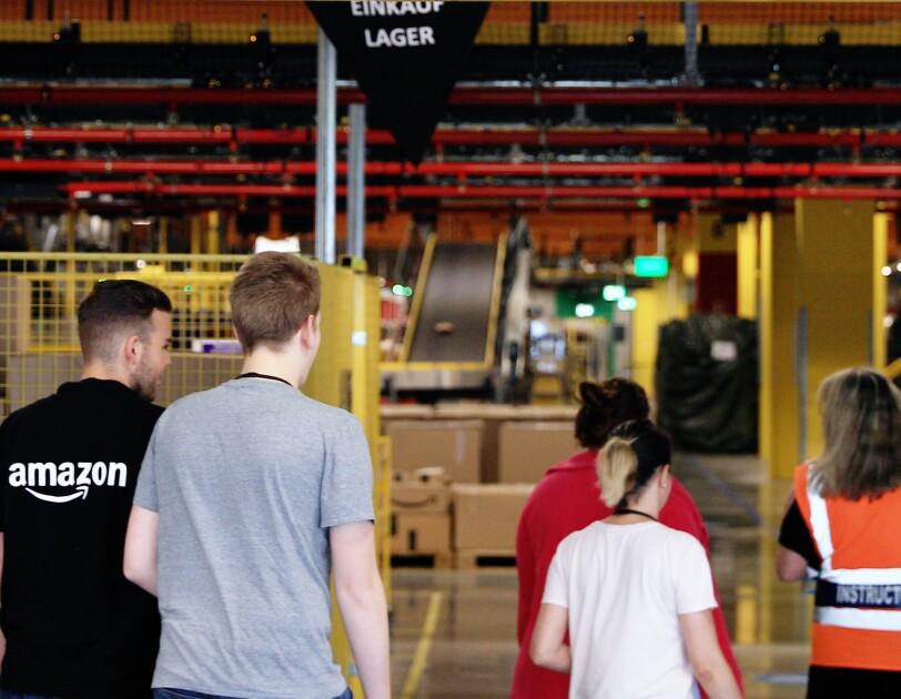 Das Team von Amazon Frankenthal im Logistikzentrum unter dem Banner: work hard. have fun. make history.
