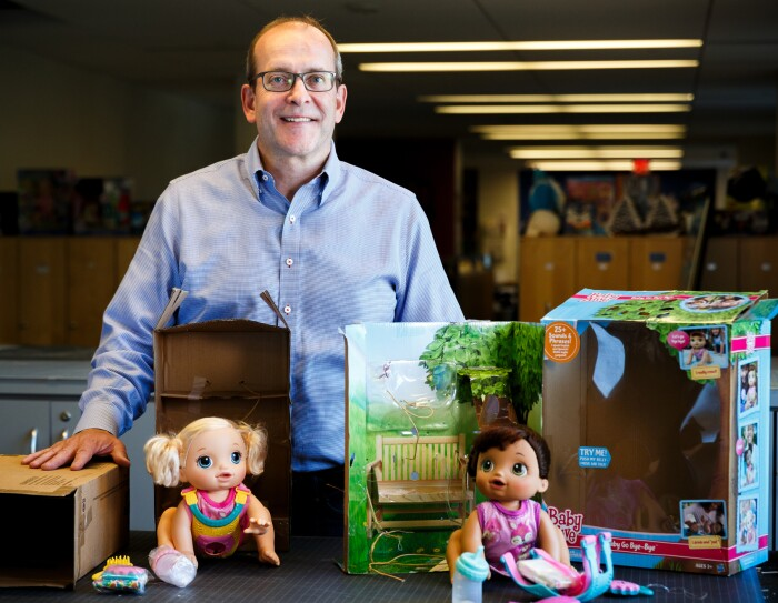 A man stands behind two toy boxes used to hold dolls.