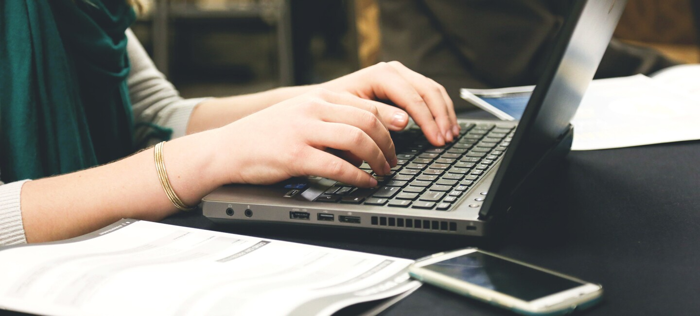 Woman working on a laptop computer, her hands are posed over the keyboard of the device.