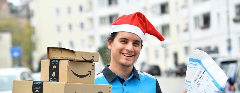 Ein junger Mann in Amazon Zustellkleidung und roter Zipfelmütze hält eine Reihe von Paketen in der Hand
