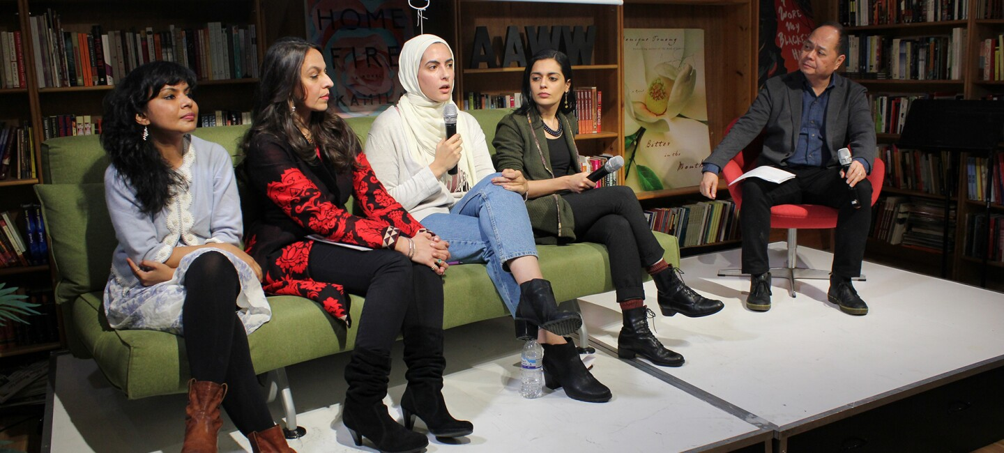 Five AAWW members, shown seated, four women sit side-by-side on a green sofa, a male sits to the right.