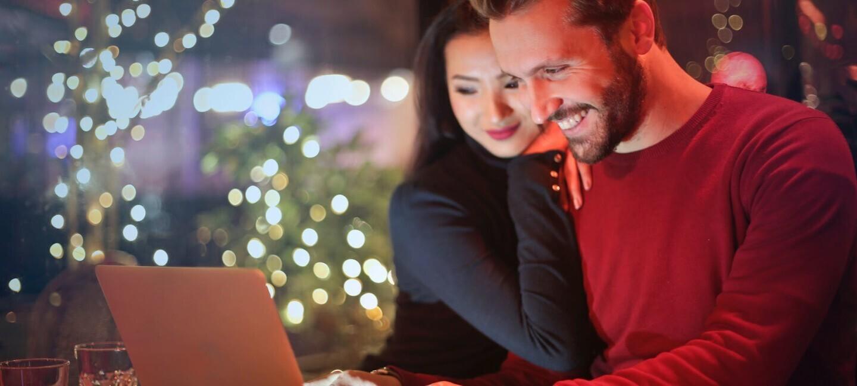 Ein Mann und eine Frau schauen lächelnd in einen hellgrauen Laptop. Im Hintergrund sind verschwommen Weihnachtsbäume und Lichter zu sehen.