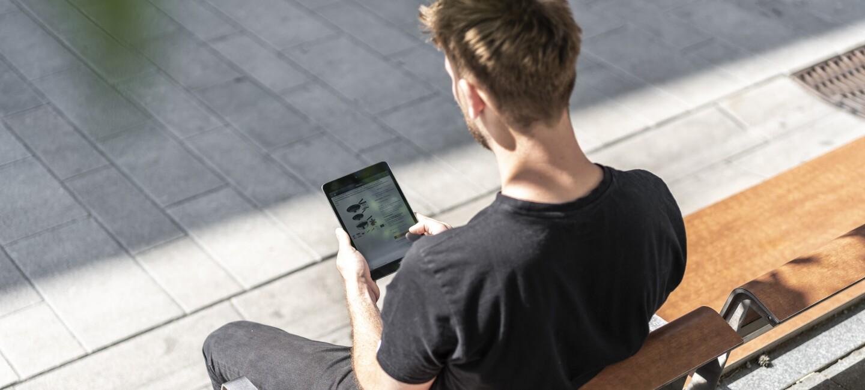 Ein junger Mann sitzt auf der Parkbank und hat ein Tablet in der Hand. Er bestellt von unterwegs bei Amazon.