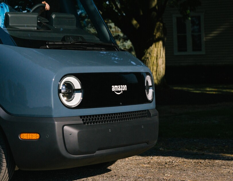 The front end of an electric delivery vehicle, showing headlights and the Amazon logo.