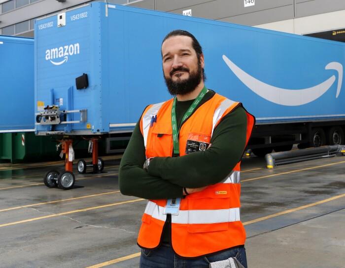 Sergio Amador con los brazos cruzados, un chaleco naranja, mira a cámara. Tiene barba y el pelo largo negro, recogido con una cola. De fondo están dos remolques azules con la sonrisa de Amazon.