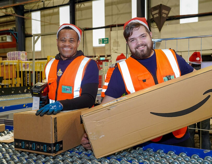 Two Amazon associates wearing santa hats, from our Belfast fulfillment center smile at the camera.