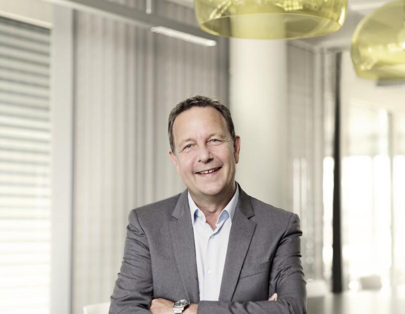 Ralf Klber trägt einen hellgrauen Anzug und lächelt in die Kamera.
