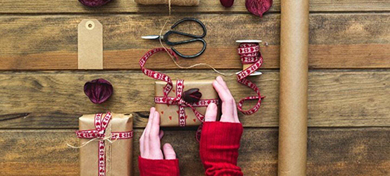 Sur une table en bois rustique, des mains portant des mitaines rouges fabriquent des paquets cadeaux avec du papier kraft, du ruban blanc et rouge et de la corde