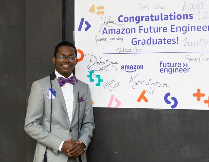 A student wears a suit and bow tie, and smiles, in front of an Amazon Future Engineer poster at his school.