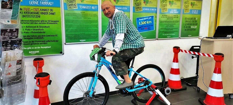 Ein Mann in kariertem Hemd und Camouflage Hose sitzt auf einem blauen Trimm-Fahrrad im Foyer eines Logistikzentrums. Im Hintergrund sind an der Wand Plakate in grün zu erkennen, die die Charity-Challenge bewerben.